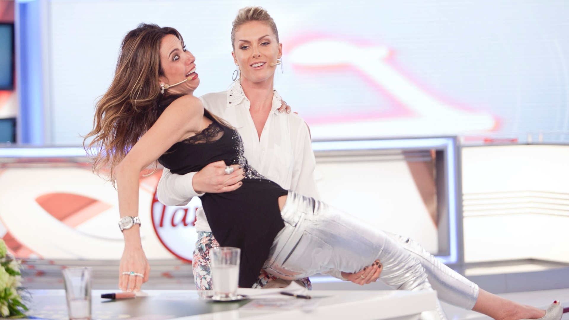 Luciana Gimenez e Ana Hickmann dão selinho demorado no palco do