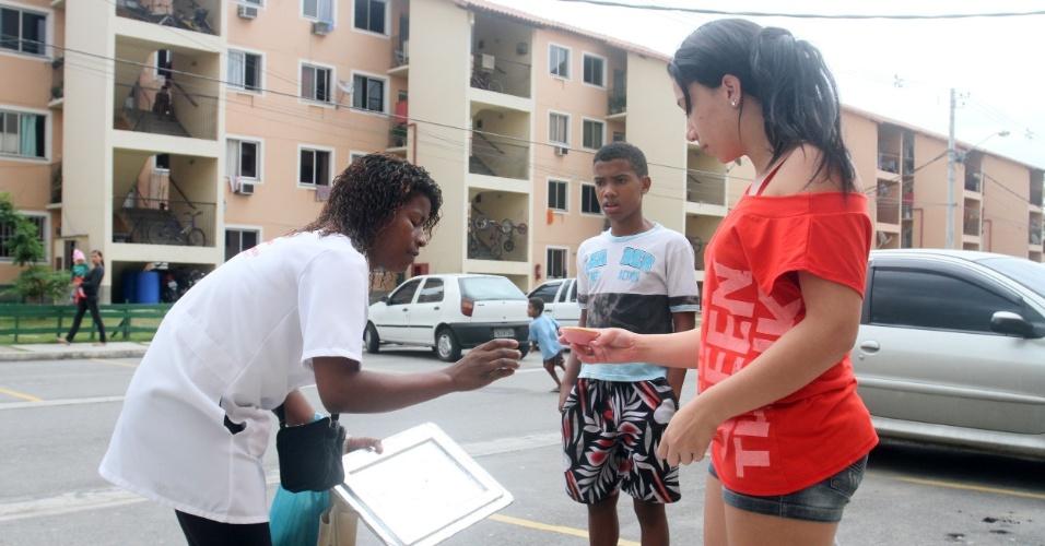 A esteticista Jéssica da Cunha compra uma empadinha de frango com Adriana em um conjunto habitacional no Alemão, no Rio (14/11/2012)