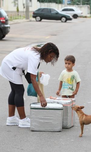 Adriana vende uma empadinha de frango para um menino em um conjunto habitacional no Alemão, no Rio (14/11/2012)
