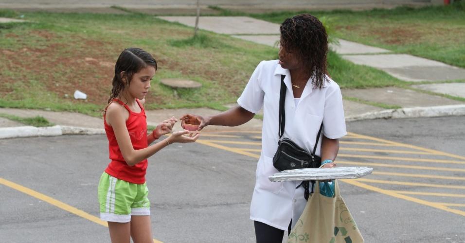 Adriana vende uma empadinha de frango para uma menina em um conjunto habitacional no Alemão, no Rio (14/11/2012)