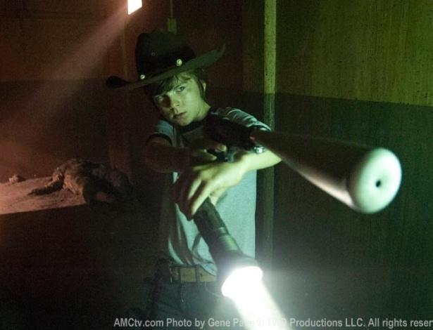"""(2012) Cena de """"Made to Suffer"""", oitavo episódio de """"The Walking Dead"""", mostra Carl (Chandler Riggs) apontado uma arma nos corredores da prisão"""