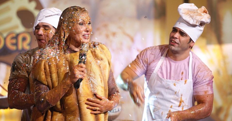 27.fev.2013 - Fantasiada de churros, Ângela Bismarchi levou um banho de doce de leite e granulado durante gravação do programa
