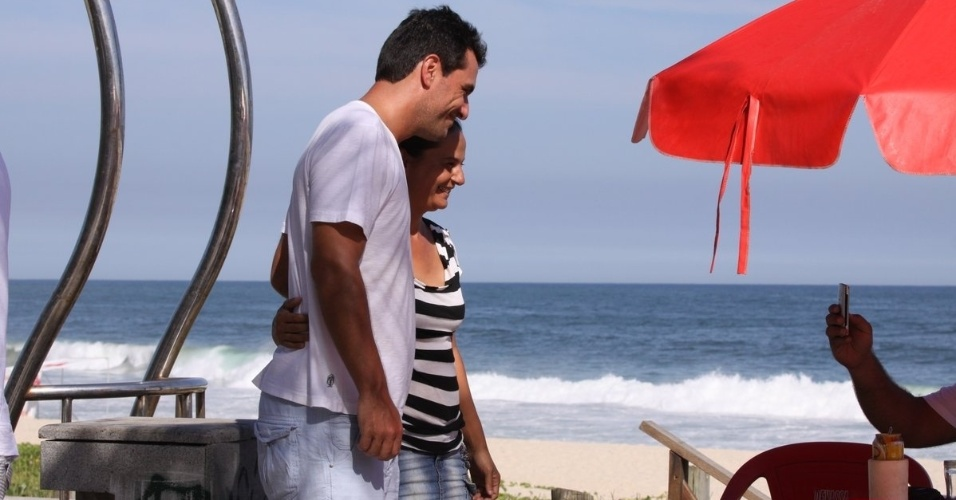 5.mar.2013 Rodrigo Lombardi grava cenas da trama de Gloria Perez na praia da Macumba, no Rio de Janeiro, e tira foto com uma fã