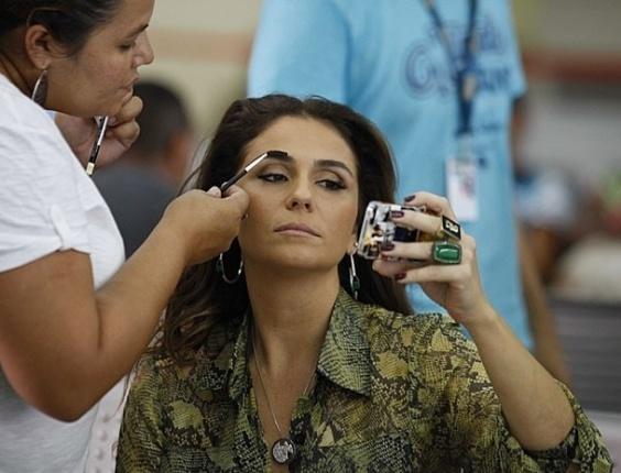 """13.mar.2013 - Giovanna Antonelli retoca a maquiagem antes de gravar cena de """"Salve Jorge"""" em aeroporto do Rio. Na trama, a atriz interpreta a delegada Helô"""