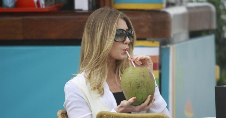 """19.mar.2013 - Letícia Spiller bebe água de coco antes do início das gravações de """"Salve Jorge"""""""