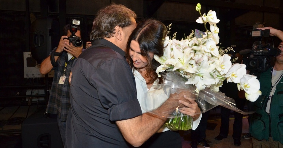 """8.abril.2013 - Dennis Carvalho entrega flores para Malu Mader e ganha um abraço da atriz na coletiva da novela """"Sangue Bom, no Projac, Rio de Janeiro"""