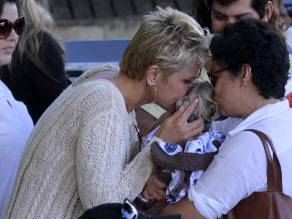 17.abr.2013 - Junto com fã, Xuxa beija seu cachorrinho Dudu, ao chegar à Prainha, no Rio de Janeiro, onde gravou o programa TV Xuxa