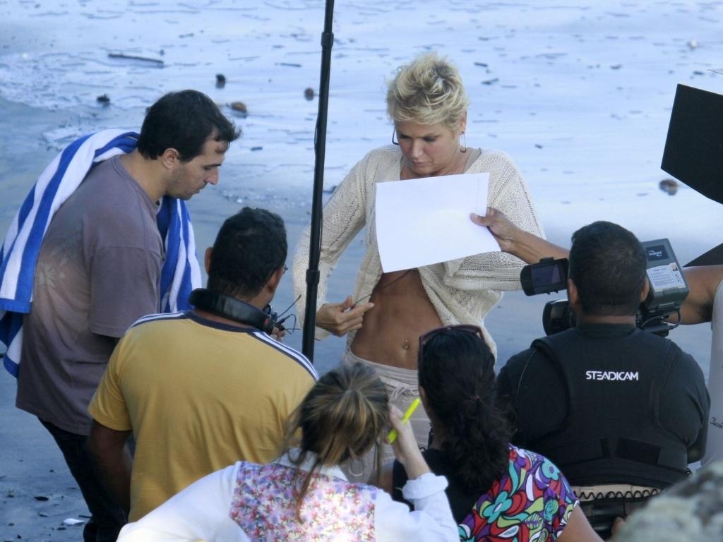 17.abr.2013 - Xuxa coloca o microfone e acaba mostrando o piercing que tem no umbigo, ao gravar TV Xuxa na Prainha, no Rio