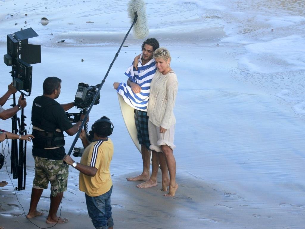 17.abr.2013 - Xuxa grava TV Xuxa na Prainha, no Rio, ao lado de surfista