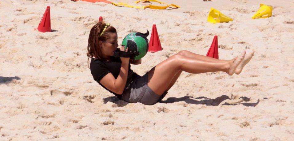 Fernanda Souza executa exercício na areia da praia da Reserva para gravação do