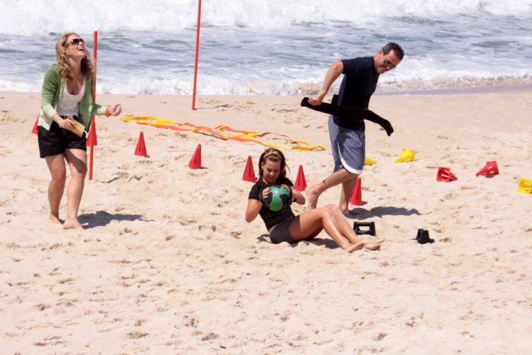 Angélica ri enquanto Fernanda Souza executa exercício na areia da praia da Reserva para gravação do