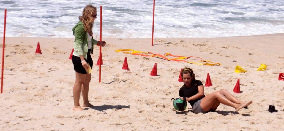 Observada por Angélica, Fernanda Souza executa exercício na areia da praia da Reserva para gravação do