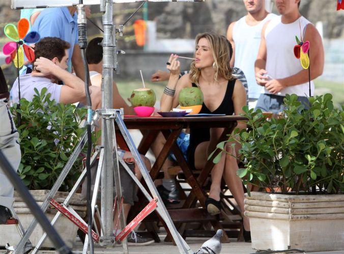 Roni Fragonard (Leonardo Miggiorin) e Deborah Secco tomam água de coco em gravação de