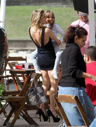 Deborah Secco segura a enteada Lara no colo em gravação da novela