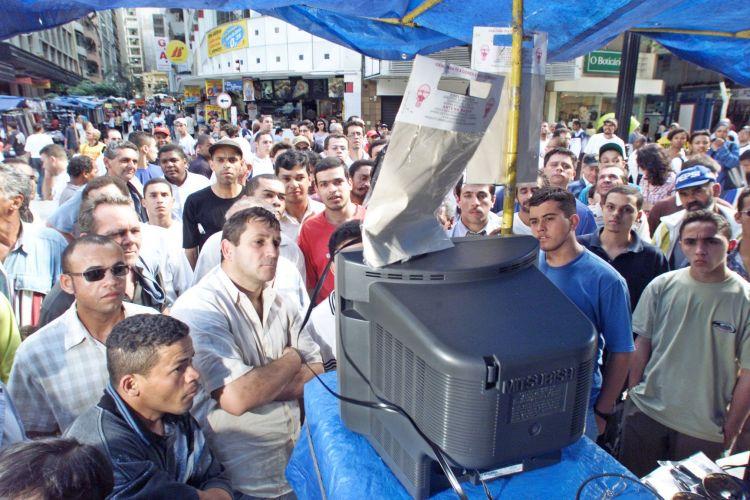 Com Silvio Santos sob a mira de sequestradores, pessoas do Brasil todo ligaram as televisões para acompanhar os desdobramentos do caso. Na foto, curiosos acompanham o sequestro por uma televisão em uma barraca de camelô, na esquina das ruas Barão de Itapetininga e Conselheiro Crispiniano, no centro de São Paulo (ago/2001)