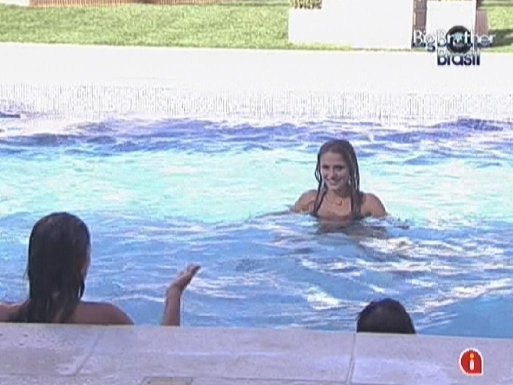 Monique (de costas) tenta atravessar a piscina sem ser