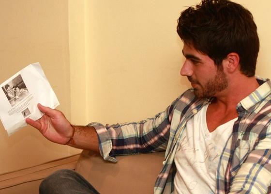Após sua eliminação, Rodrigão olha a foto que circula pela internet (22/3/11)