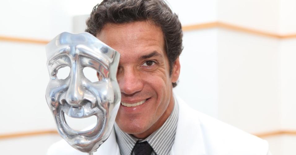 Carlos Machado posa ao lado de uma máscara do teatro em seu consultório na zona sul carioca (26/1/12)