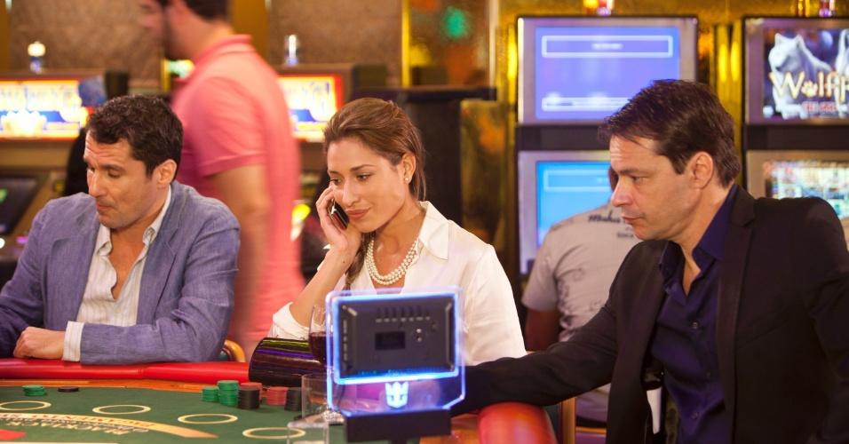 Manu (Giselle Itié) fala ao celular com Nameless (Paloma Duarte). Martim (Heitor Martinez) e Caio jogando no cassino do navio