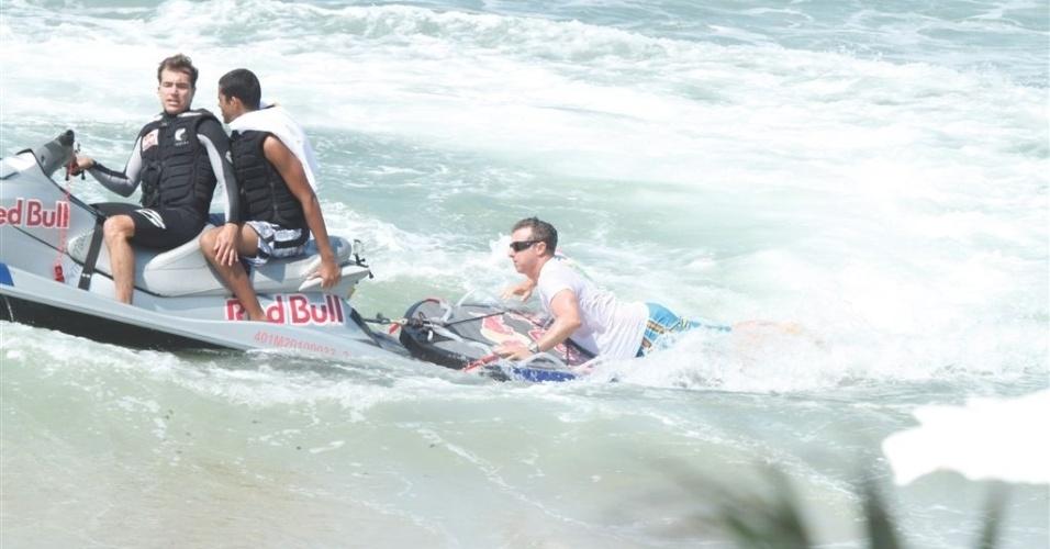 """Às 7h da manhã, Luciano Huck gravou matéria para o """"Caldeirão"""" com um surfista deficiente visual na praia da Macumba, no Rio de Janeiro. O apresentador levou o jovem para ter uma aula de surfe com o campeão de ondas gigantes Carlos Burle (15/3/12)"""