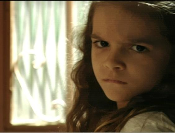 Rita (Mel Maia) ouve Carminha (Adriana Esteve) ao telefone combinando plano para roubar dinheiro de Genésio (Tony Ramos)