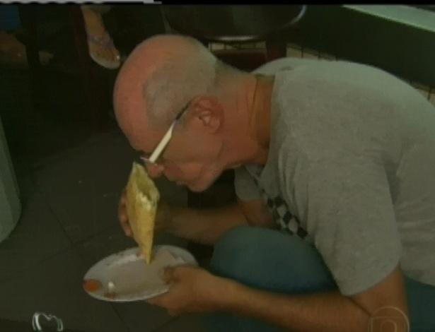 Marcos Caruso come um pastel durante visita no Mercadão de Madureira (25/4/12)