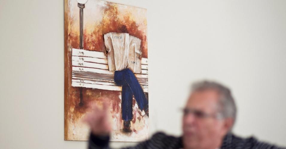 """Na sala de estar, dividida em três partes, um quadro com a imagem de um homem sentado em um banco, lendo jornal, com os dizeres: """"A Praça"""", ilustra uma das paredes. """"Esse foi um presente do Marcelo, não conheço o artista que pintou"""", afirma Nóbrega (4/5/12)"""