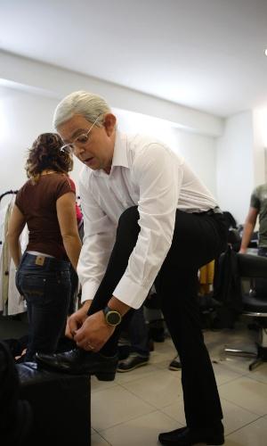Já maquiado, Carioca começa a vestir parte do figurino dao jornalista Boris Casoy, camisa, terno e gravata