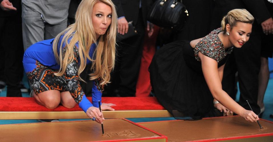 Britney Spears faz careta enquanto assina o nome no cimento do Grauman's Chinese Theatre ao lado de Demi Lovato (12/9/12)