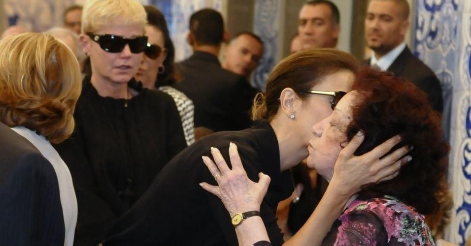Ivete Sangalo dá um beijo em Lolita Rodrigues durante a missa de sétimo dia de Hebe Camargo na igreja Nossa Senhora do Brasil, em São Paulo (5/10/12). Ao fundo, a apresentadora Xuxa