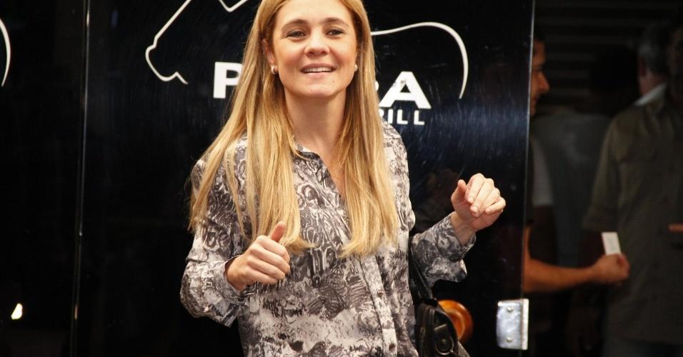 A intérprete de Carminha, Adriana Esteves, acena na entrada do encontro com o elenco da novela (19/10/12)