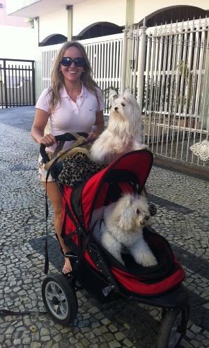 Franci Bonates, a dona de Emily e Charlote, leva as cadelinhas para passeio em um carrinho de bebê