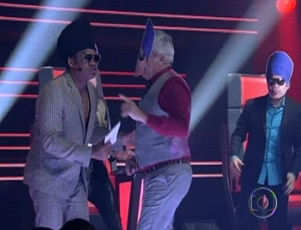 """Lulu Santos e Daniel (ao fundo, á dir) usam máscara com rosto de Carlinhos Brown em homenagem ao aniversário do músico na terceira semifinal do """"The Voice Brasil"""" (25/11/12)"""