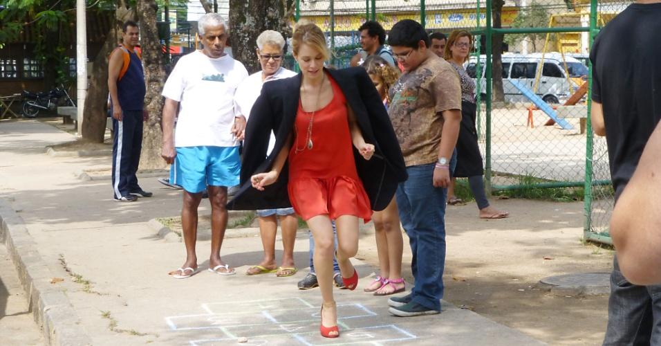"""Mariana Ximenes, a Juliana da novela """"Guerra dos Sexos"""", gravou cenas da trama na feira de rua no Largo do Pechincha, Zona Oeste do Rio de Janeiro. A empresária pula amarelinha e se sente realizada (21/11/12)"""