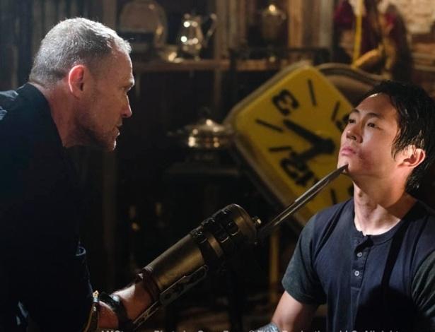 """(2012) Em """"Hounded"""", sexto episódio da terceira temporada de """"The Walking Dead"""", Merle (Michael Rooker) ameaça Glenn (Steven Yeun) para tentar descobrir onde é a prisão em que seu irmão Daryl (Norman Reedus) está escondido"""