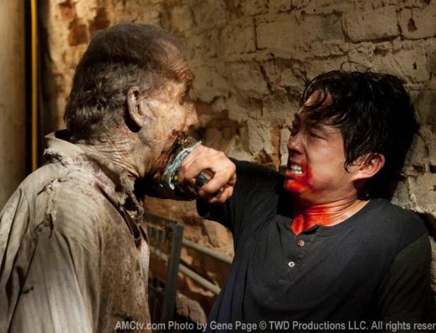 """(2012) Sequestrado por Merle (Michael Rooker) e preso em Woodbury, Glenn (Steven Yeun) é atacado por um zumbi em cena do sétimo episódio da terceira temporada de """"The Walking Dead"""""""
