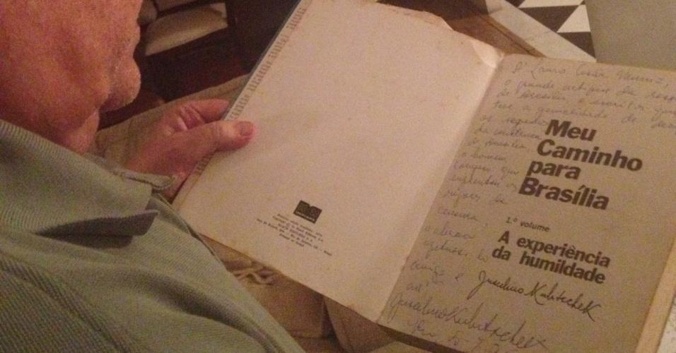 """Autor Lauro César Muniz folheia livro autografado pelo presidente JK, cujas imagens foram vetadas pela censura na novela """"Escalada"""", que retratava a construção de Brasília"""