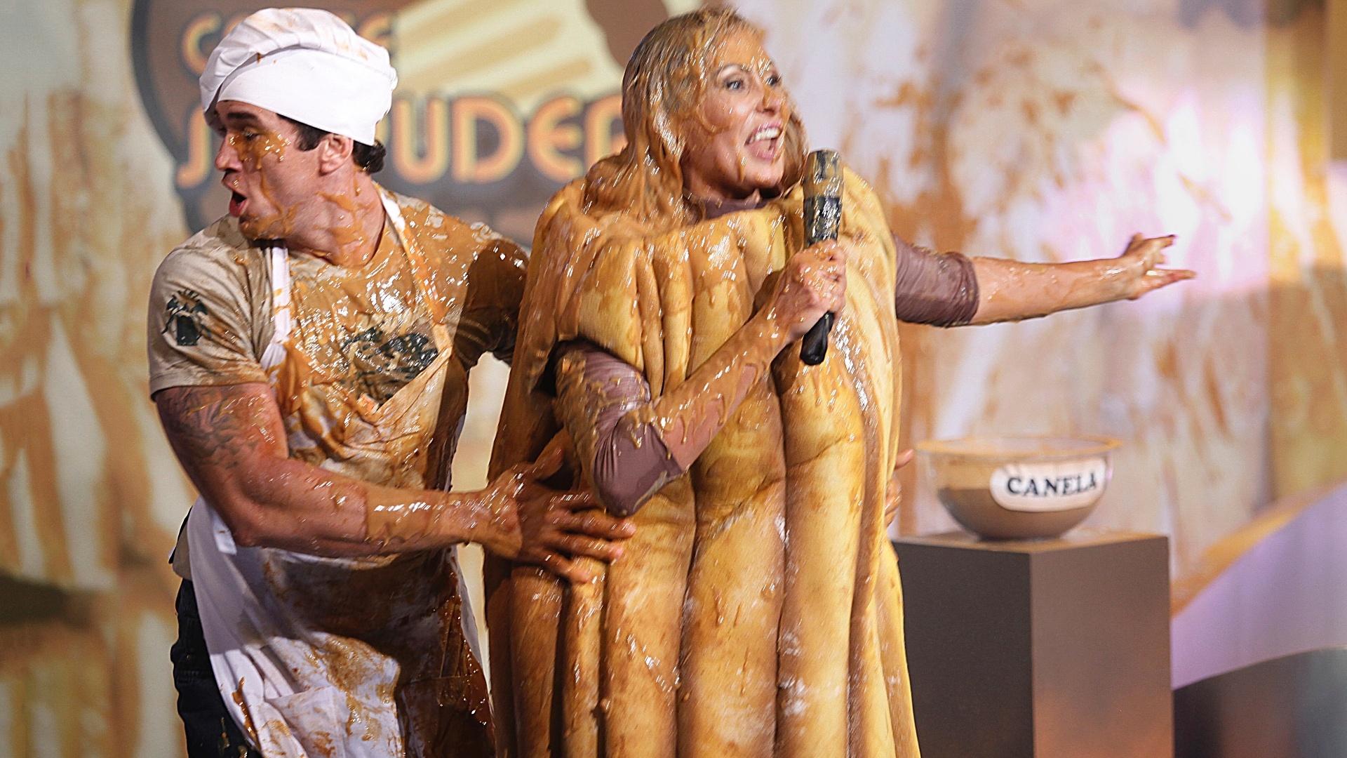27.fev.2013 - Fantasiada de churros, Ângela Bismarchi levou um banho de doce de leite durante gravação do programa