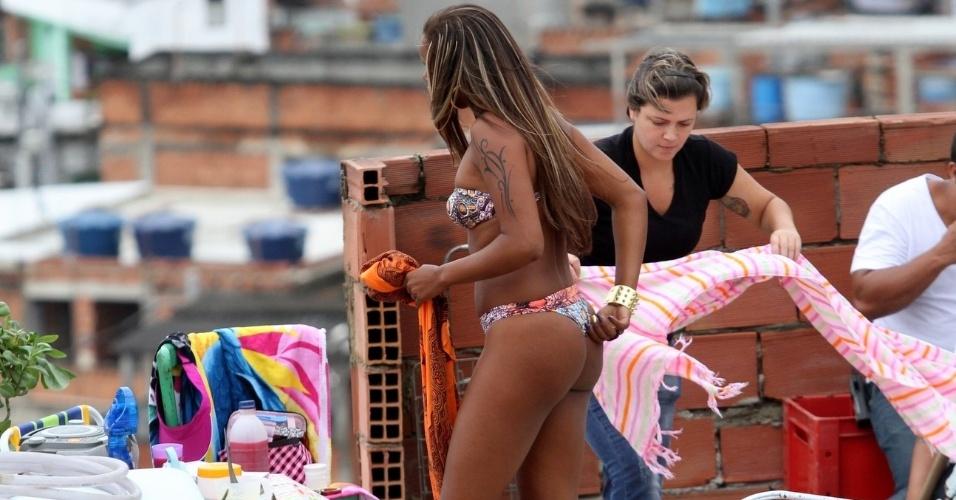 19.mar.2013 Roberta Rodrigues ajeita o biquíni durante a gravação de mais uma cena onde sua personagem, Maria Vanúbia, estará tomando sol na lage