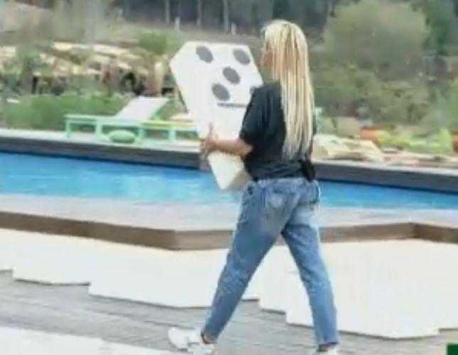 Monique Evans leva peça para o centro do deck, que funciona como um tabuleiro gigante (01/10/11)