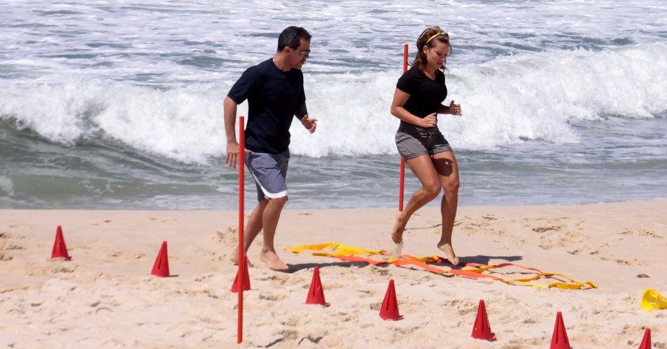 Um personal trainer instrui Fernanda nos exercícios, gravados para o programa
