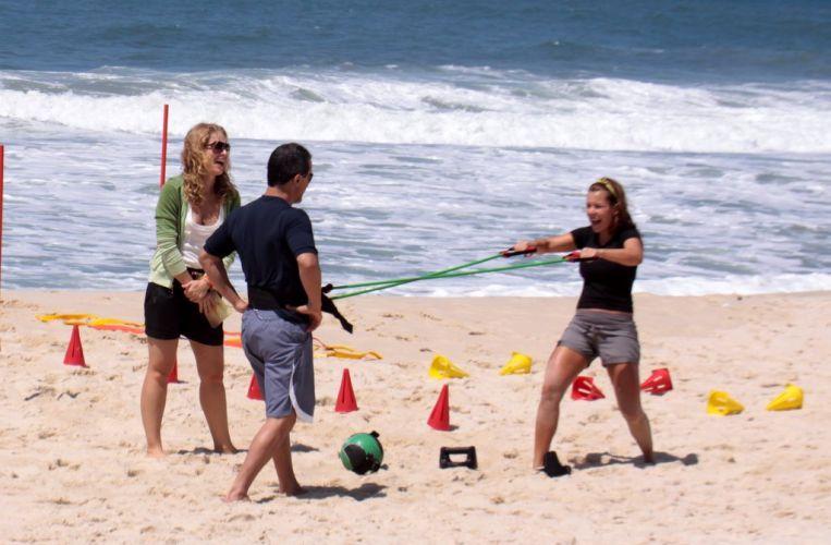 Com a ajuda do personal trainer, Fernanda Souza executa exercício na areia da praia da Reserva para gravação do