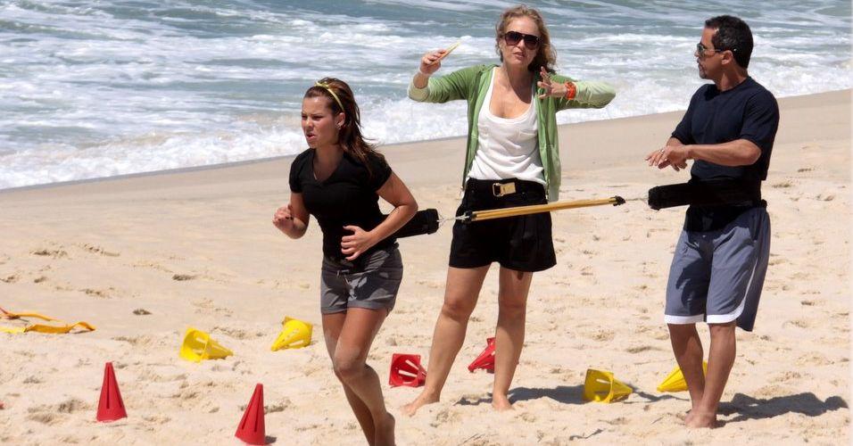 Angélica gesticula enquanto Fernanda Souza executa exercício com a ajuda do personal trainer (3/11/2010)