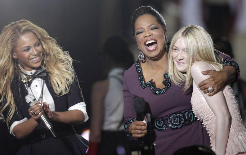 A apresentadora Oprah Winfrey abraça a atriz Dakota Fanning (dir.), enquanto é observada pela cantora Beyoncé, na gravação do último programa