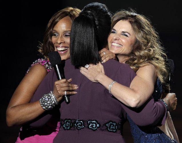 A apresentadora Oprah Winfrey (de costas) recebe o abraço das jornalistas e amigas Gayle King (esq.) e Maria Shriver (dir.), a ex-mulher de Arnold Schwarzenegger, que acabou de descobrir que ele teve um filho fora do casamento. O programa será dividido em duas partes e será exibido nos dias 23 e 24 de maio nos Estados Unidos
