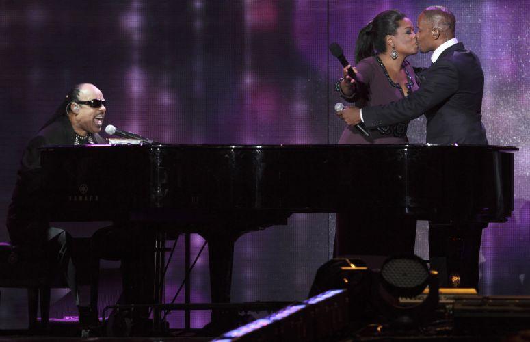 Oprah Winfrey ganha um selinho do ator e cantor Jamie Foxx durante apresentação do cantor Stevie Wonder (esq.) na gravação do último