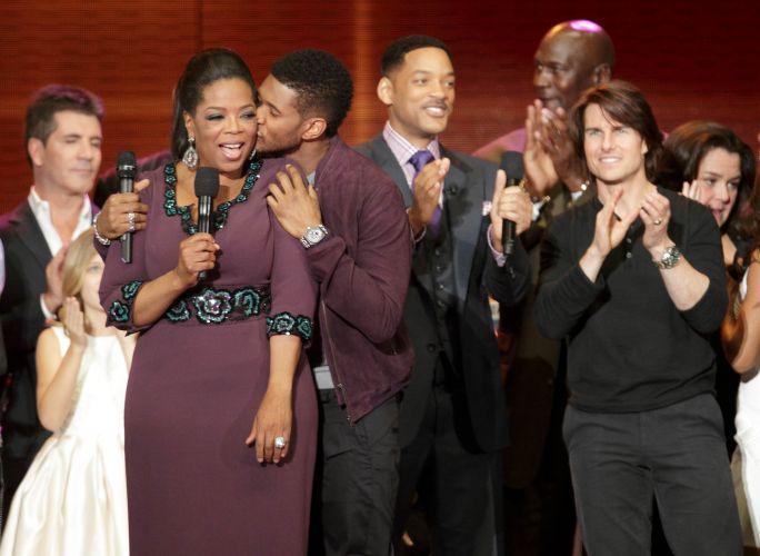 Oprah Winfrey recebe um beijo do cantor Usher na gravação do último