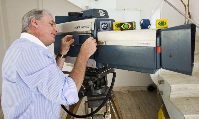 Otávio Mesquita posa ao lado de uma antiga câmera e com os cubos de microfone das emissoras em que já trabalhou (12/5/2011)