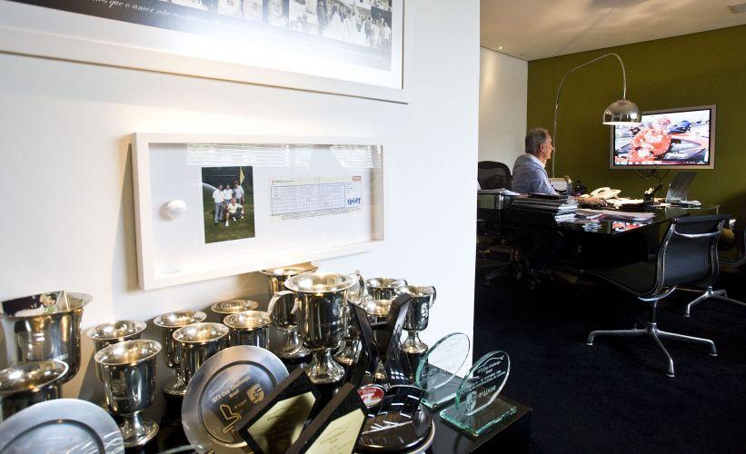 Detalhe na mesa do escritório de Otávio Mesquita repleta de troféus que ganhou nas corridas que disputou, em diversas categorias do automobilismo. Na parede, o quadro com foto e uma bolinha de golfe, de acordo com o apresentador sua