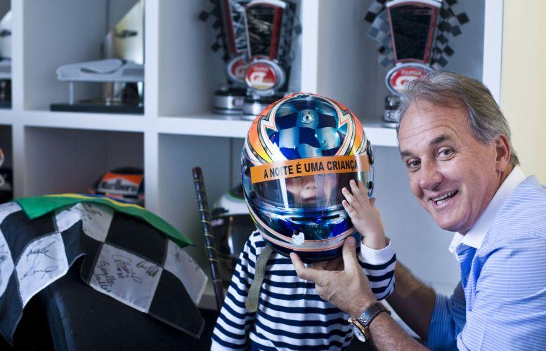 O apresentador Otávio Mesquita coloca um de seus capacetes na cabeça do filho Pietro, 2, que mesmo pequeno já demonstra também gostar de automobilismo (12/5/2011)